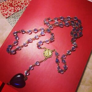 rosary beads on red book